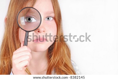 girl looking through magnifying glass - stock photo