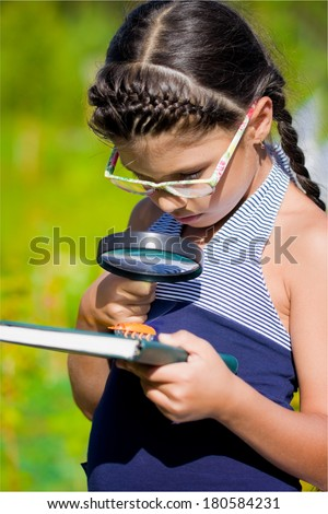 girl looking through magnifying glass on beetle - stock photo