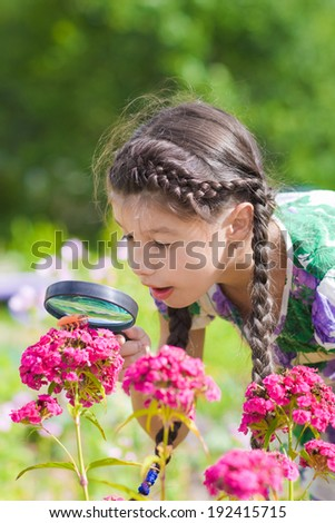 girl looking through magnifying glass on flower - stock photo