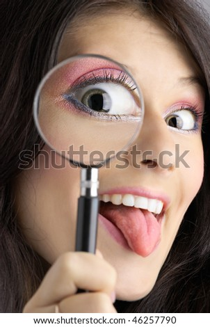 Girl looking through the magnifying glass with tongue hanging out - stock photo