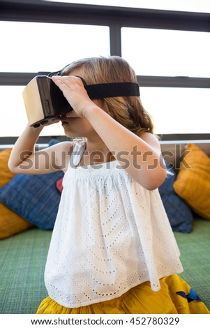 Girl looking through virtual reality headset while sitting on couch in school library - stock photo