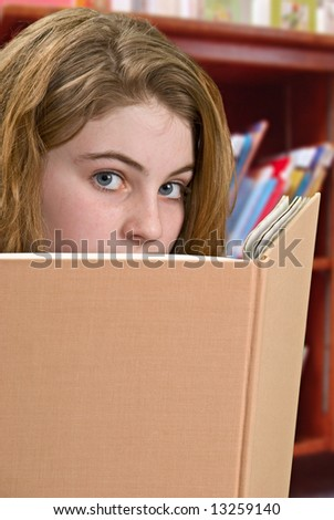 Girl looking up from book - stock photo
