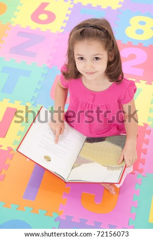 Girl looking up from reading book on colorful alphabet floor mat. - stock photo