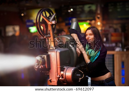 girl looks at an old movie projector - stock photo