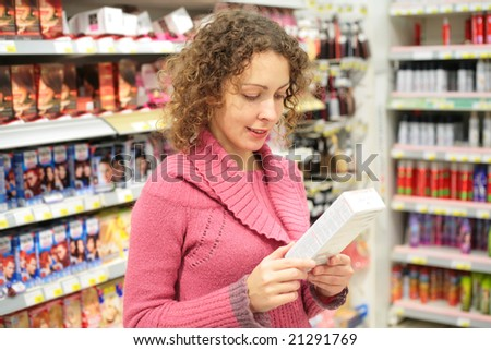 Girl looks at box with goods in hands in store - stock photo