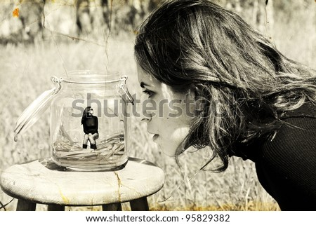 girl looks at herself in the glass jar. Photo in old image style. - stock photo