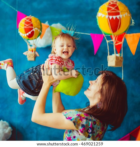 Girl looks funny while mother throws her up in the air