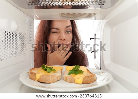 Girl looks in a microwave and yawn