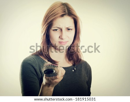 girl looks in disgust at the remaining hair on the comb after combing on a white background isolated - stock photo