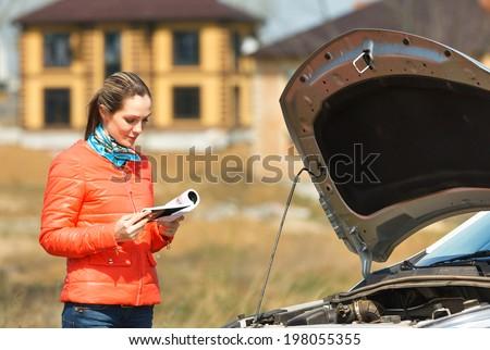 girl looks in  user manual in  broken down car  hood open - stock photo