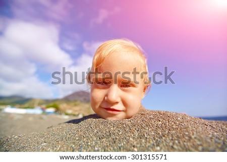 girl looks into the camera on the sunny beach over a blue sky - stock photo