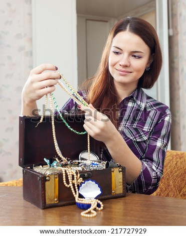 girl looks jewelry in treasure chest at home  - stock photo