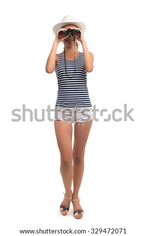 Girl looks through binoculars on a white background. Girl spying. Sexy girl. Playful girl in shorts. - stock photo