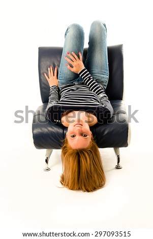 Girl lying face down on a stylish easy chair - stock photo