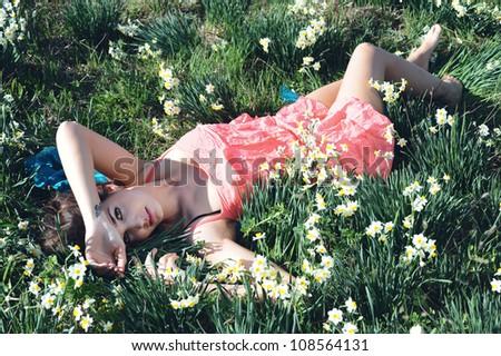 girl lying in a field of flowers - stock photo