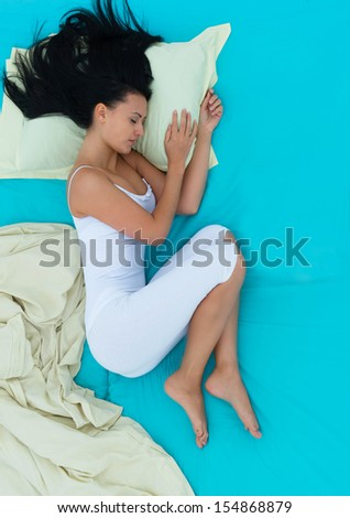 Girl lying in bed and sleeping, view from above - stock photo