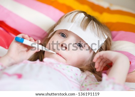 girl lying in bed with a thermometer - stock photo