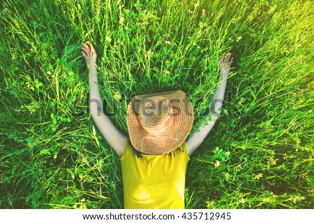 girl lying in grass with straw hat in summer sun