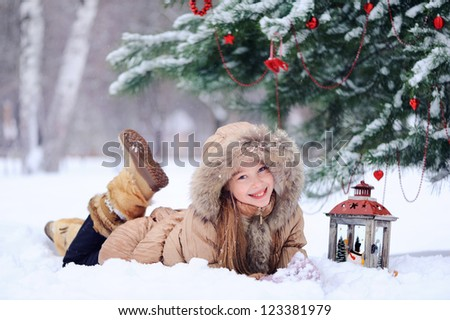 Girl lying in the snow and laughs. Against the background of the Christmas tree. - stock photo