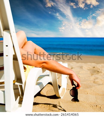girl lying on a beach lounger with glasses in hand against blue sky - stock photo
