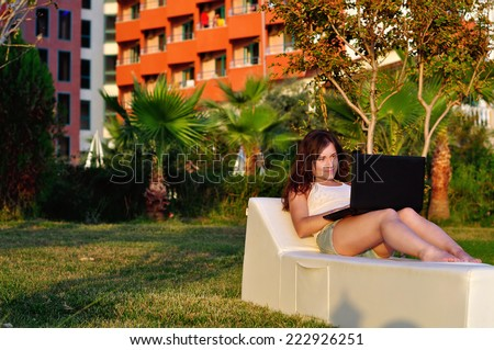 Girl lying on a deck chair and working on a laptop - stock photo