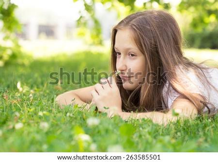girl lying on a grass and holding a flower
