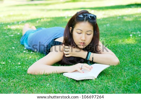 Girl lying on a grass and reading a book