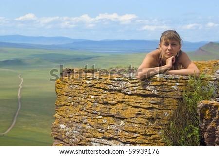 Girl lying on a rock - stock photo