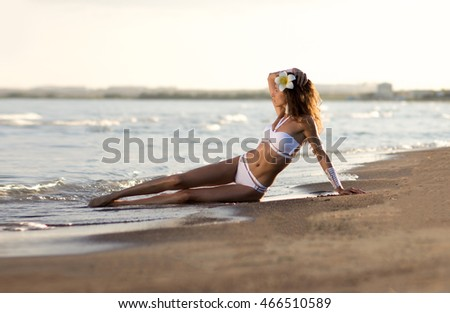 Girl lying on a sandy beach in a white bathing suit with a flower in her hair