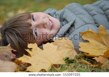 girl lying on autumn leaves