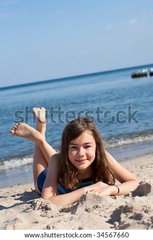 Girl lying on beach - stock photo
