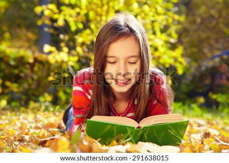 girl lying on fallen leaves  in the park and reading a book. reading, learning and education in autumn - stock photo