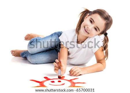 Girl lying on floor and painting a happy sun - stock photo