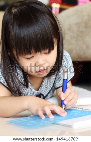 Girl lying on floor while writing using a stencil and pen