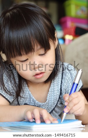 Girl lying on floor while writing using a stencil and pen - stock photo
