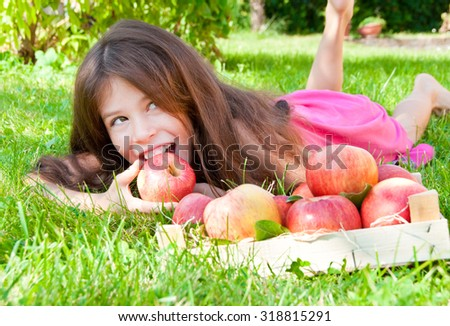 Girl lying on grass and eating apples  - stock photo