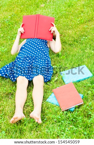 Girl lying on grass and reading a book - stock photo