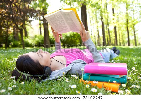 girl lying on grass and relaxing  with book and music - stock photo