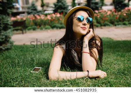 Girl lying on grass in city square and talking on phone - stock photo
