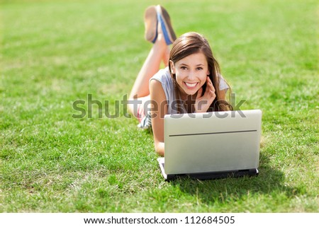 Girl lying on grass with laptop