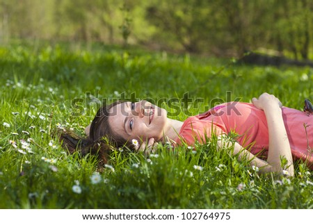 Girl lying on green grass - stock photo