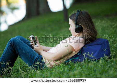 Girl lying on green grass outdoors in summer or spring reading her cellphone or tablet and wearing headphones
