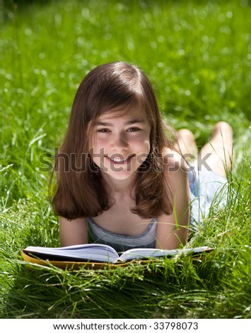 Girl lying on green meadow reading book