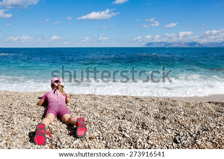 Girl lying on her belly, observing sea and enjoying free time on the beach, dressed in wetsuit and a hat for sun protection. Family and children on vacation, summer fun concept.  - stock photo