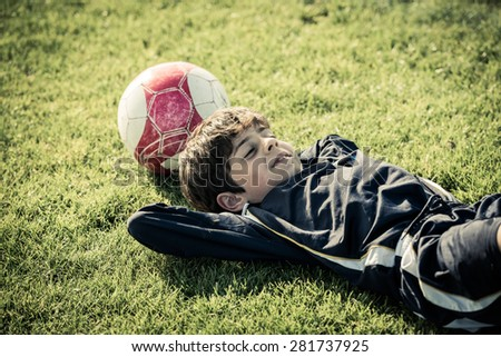Girl lying on soccer field after the game - stock photo