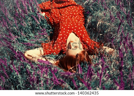 Girl lying on spring grass and flowers. Photo in 40-s cinema colour style. - stock photo