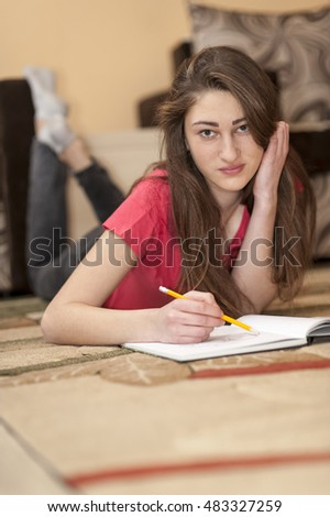 girl lying on the carpet and draws something in a notebook