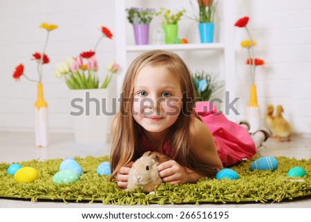 girl lying on the carpet with a rabbit - stock photo