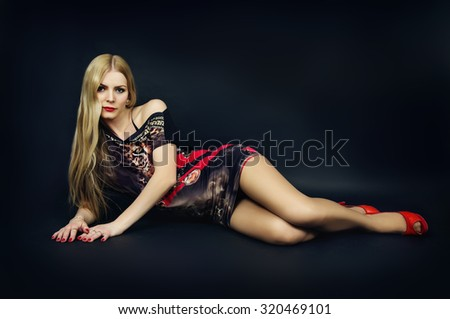 Girl lying on the floor in the studio on a black background - stock photo