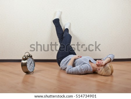 Girl lying on the floor of an empty room with my feet up next to the clock , closing his eyes